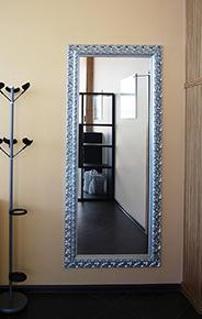 Зеркало в серебряном багете на стене